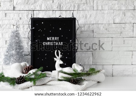 Merry Christmas text made with white letters on a black wooden board with knitted sweaters, deer figurine, silver Christmas tree and fir branches on white table, bright white brick wall background