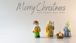 Merry Christmas text with figures of a Bethlehem portal, with Saint Joseph, the Virgin Mary and the baby Jesus with hygienic masks due to the Covid-19 pandemic. Concept New Normal