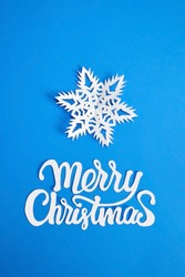 Merry Christmas text with white snowflake on blue paper background. Christmas holidays greeting card design.