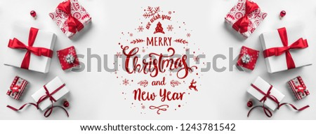 Merry Christmas Typographical on white background with gift boxes and red decoration. Xmas and New Year card. Flat lay, top view #1243781542