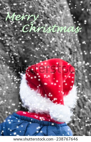 Merry christmas wish with little christmas elf in front of a huge tree in the snowy forest/Winter Christmas Imp with red pointed Hat and textual Christmas Wish