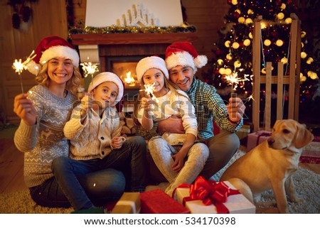 Merry Christmas with sparklers- family celebrating Christmas eve