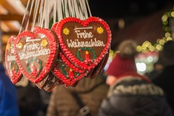 Merry Christmas written in German on gingerbread hearts at a Christmas market close up
