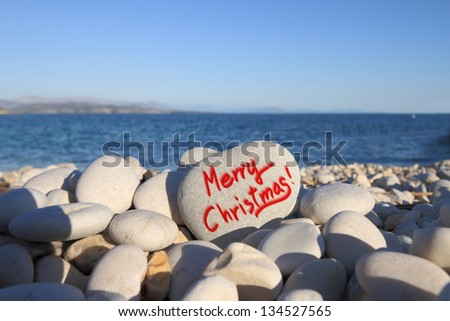 Merry Christmas written on heart shaped stone on the beach with spray brush