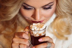 Merry Christmas. Young woman dressed warmly, drinking hot chocolate.