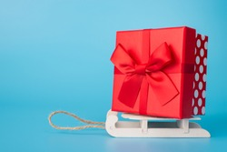 Merry Chrristmas and Happy new Year! Best wishes! Photo poster banner postcard of big nice packed present box standing on small sledges isolated over blue background