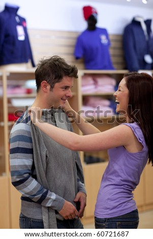Merry couple looking for a sweat-shirt in a clothes store