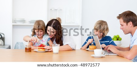 Merry family eating breakfast in the kitchen at home