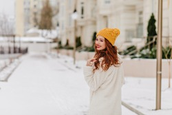 Merry ginger woman looking back while walking around winter city. Graceful european girl chilling in snowy morning.