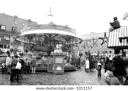 Merry-go-round in Neurenburg - Munich at Christmas time.  Movement on people and merry-go-round.  Black-and-white.