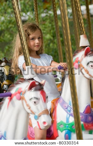 Merry-go-round - little girl playing on carousel