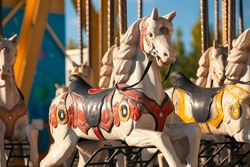 Merry-go-round wooden horses at amusement park. Vintage carousel pony at luna park.