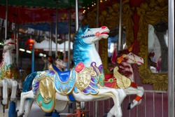 merry-go-round wooden horses, Carousel Horse with traditional paintwork. Beautiful horse Christmas carousel in a holiday park. Two horses on a traditional fairground vintage carousel. Merry-go-round
