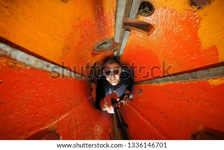 Merry Selfie young guy with glasses in the torpedo compartment of a submarine. Painted in orange, the concept of confined space, selfie in the tube. Wide leg