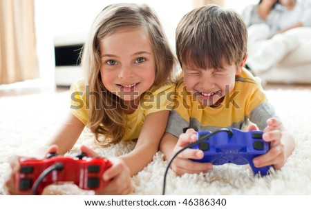 Merry siblings playing video game in the living room