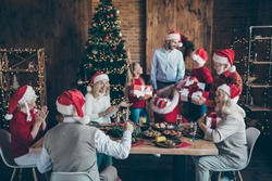Merry x-mas meeting joyful small little kids mature pensioner sit table with christmas meal santa claus cap hat man hold sack bag give giftbox wish dream in house with newyear ornament decoration