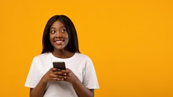 Merry young black lady in casual outfit using modern smartphone and looking at copy space, reading exciting advertisement, yellow studio background, panorama. Mobile application concept