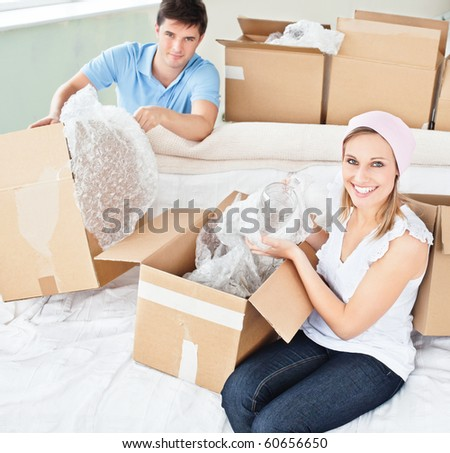 Merry young couple unpacking boxes with glasses in their new house - stock photo