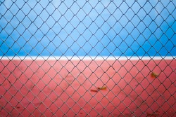 Mesh Fence with blue and red background.