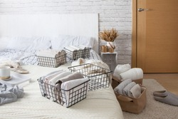Mesh metal containers full of clothes and linen stand on the bed and on the floor in the bedroom with cup of coffee during general cleaning. Concept of updating and organizing
