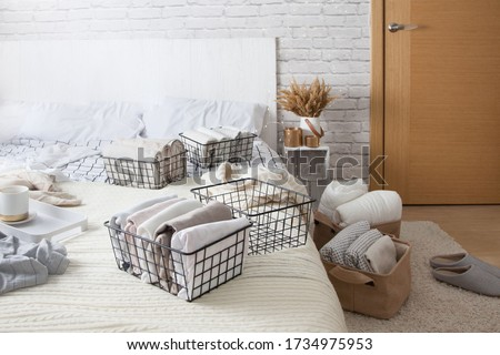 Mesh metal containers full of clothes and linen stand on the bed and on the floor in the bedroom with cup of coffee during general cleaning. Concept of updating and organizing Stockfoto ©