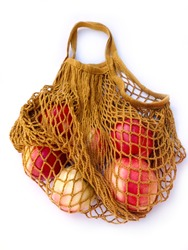 Mesh shopping bag with peaches on white background. Caring for the environment and the rejection of plastic concept
