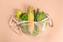 Mesh string bag with green vegetables and herbs on a beige background. Sustainable lifestyle. Eco-friendly concept. Top view