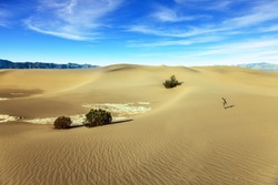 Mesquite Flat Sand Dunes, Death Valley, California. Elderly woman with a camera and a tripod goes among the dunes. Light sand waves from the desert wind. Concept of active and photo tourism