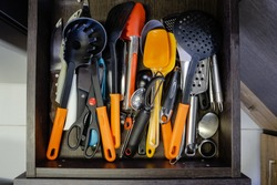 Mess in the cutlery drawer. Top view of various kitchen utensils without organization. Predominance of orange color.