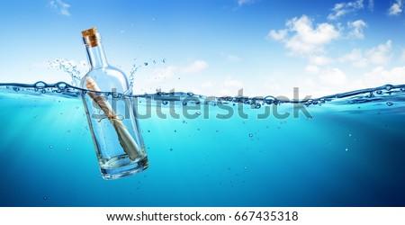 message in bottle floating in...