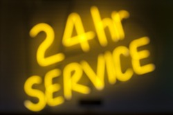 Message in yellow neon on black background for 24 hour service