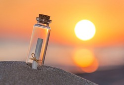 Message sheet in a bottle at sea beach sand against bright sunset