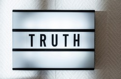 Message Truth on illuminated board. Truthfulness concept with text. Daylight from window. Room interior. Black letters Truth on white wallpaper wall.