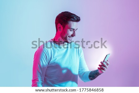Messages from social network. Smiling young man look at luminous smartphone in neon light, copy space