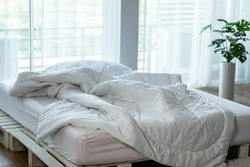 Messed bed with white pillow and duvet blanket with natural light in bedroom in the morning, Messy bed after wake up, Messy bed and Cozy Bedroom Concept