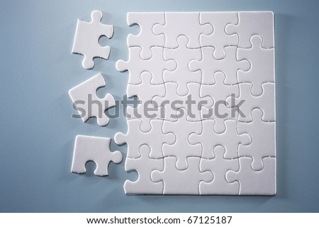 Messed up jigsaw puzzle isolated on the blue background.