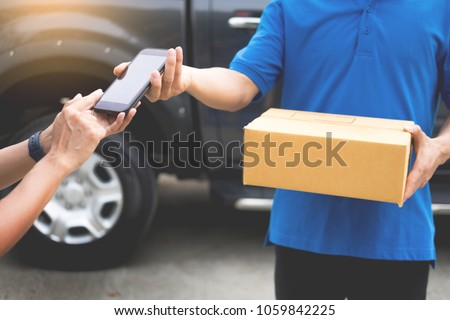 messenger man hold box and talk on smart phone and payment terminal in hands, Package delivery concept #1059842225