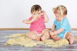 Messy baby toddlers having fun eating pasta