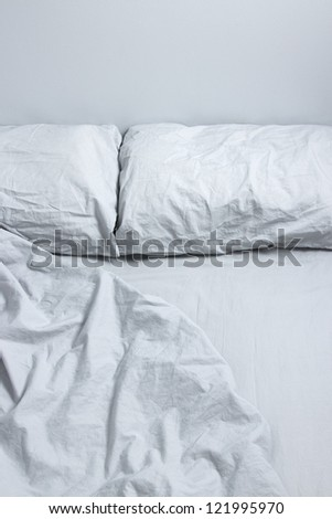 Messy bed with two pillows and gray bedclothes.