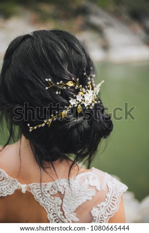 Messy bridal updo hairstyle with elegant hairpin jewelry on dark hair #1080665444