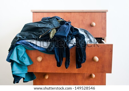 Messy brown chest of drawers with  dangling mixed man's and woman's clothes.