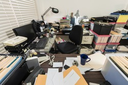 Messy business office with piles of files and disorganized clutter.