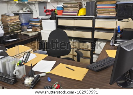 Messy, busy desk in a warehouse back office.