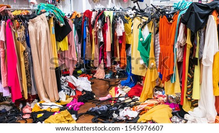 Messy clearance section in a clothing store, with colorful garments on racks and on the floor; fast fashion concept