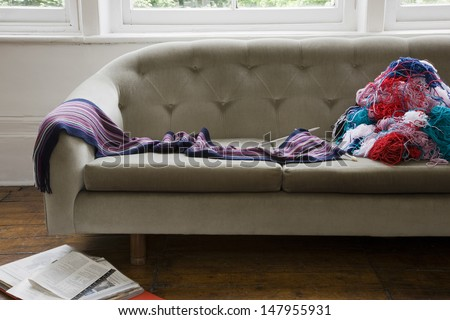 Messy colorful wool threads on sofa in the house