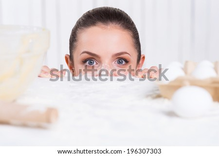 Messy cooking. Playful young woman with flavor on face looking out of the kitchen table