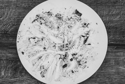 messy Cutlery.  filthy plate. Dirty dish after eating. Dining background. Black and white photo
