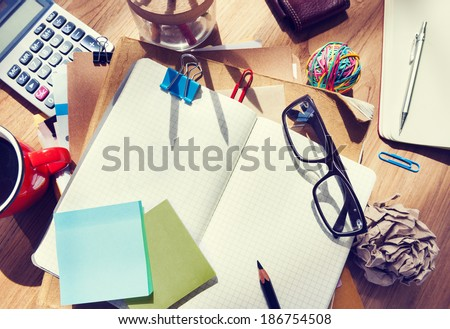 Messy Designer\'s Table with Blank Note and Tools