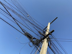 Messy electrical cables and wires on electric pole. blue sky background.