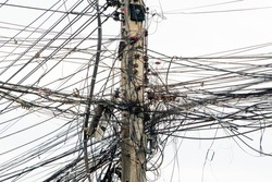 messy electricity wires on the pole, The chaos of cables and wires on an electric pole in Thailand
